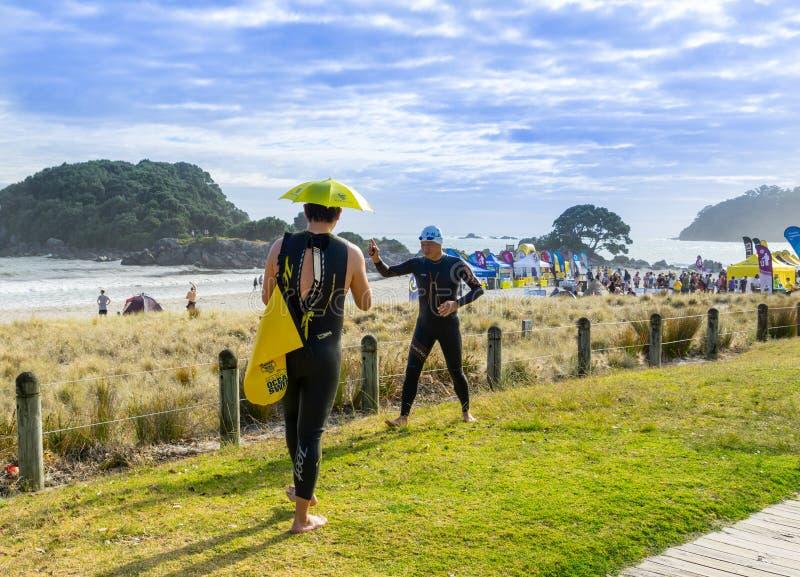 Konkurrenter och åskådare för utvecklingshemmen sandpapprar för att surfa badhändelse på mulen dag arkivbilder