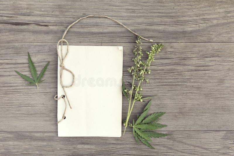Konopie opuszcza i kwitnie z handmade rzemiosło notatnikiem na starego grunge drewnianym tle Odgórny widok Minimalistic mockup zdjęcie stock