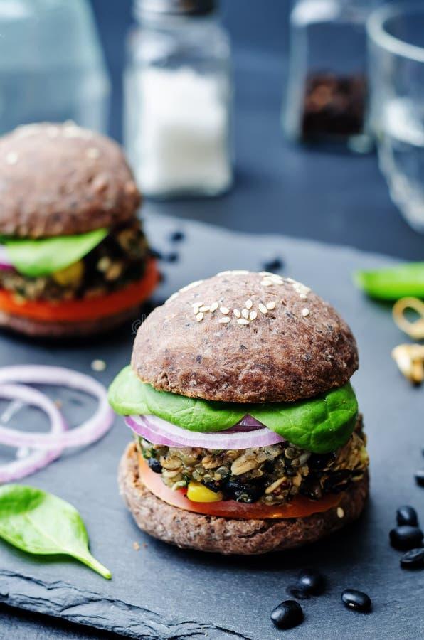 Konserverar spenat för svart böna för Quinoa hamburgare med bullecrusen för svarta bönor arkivbild