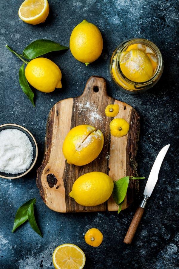 Konservierte, gesalzene in Büchsen konservierte Zitronen auf einem hölzernen Brett über schwarzem Steinhintergrund Marokkanische  stockbilder