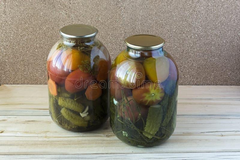 Konserwować ogórki w i pomidory szklani słoje obrazy stock