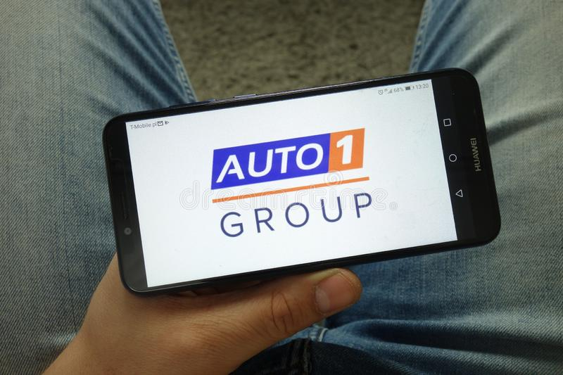Man holding smartphone with Auto1 Group car trading platform logo. KONSKIE, POLAND - April 13, 2019: Man holding smartphone with Auto1 Group car trading platform stock photos