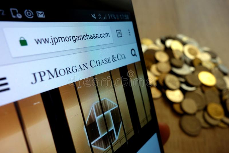 JP Morgan Chase website displayed on smartphone and stack of coins royalty free stock image