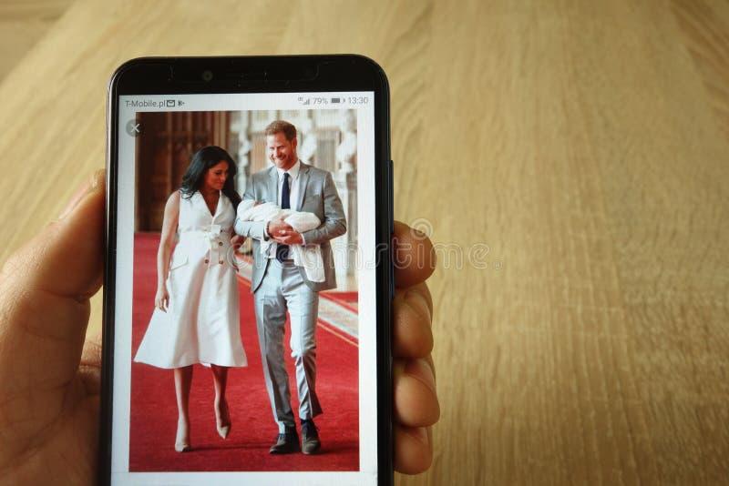 KONSKIE POLSKA, Maj, - 18, 2019: wr?cza mienia smartphone z fotografi? ksi??e Harry Markle z dzieckiem i Meghan obrazy royalty free