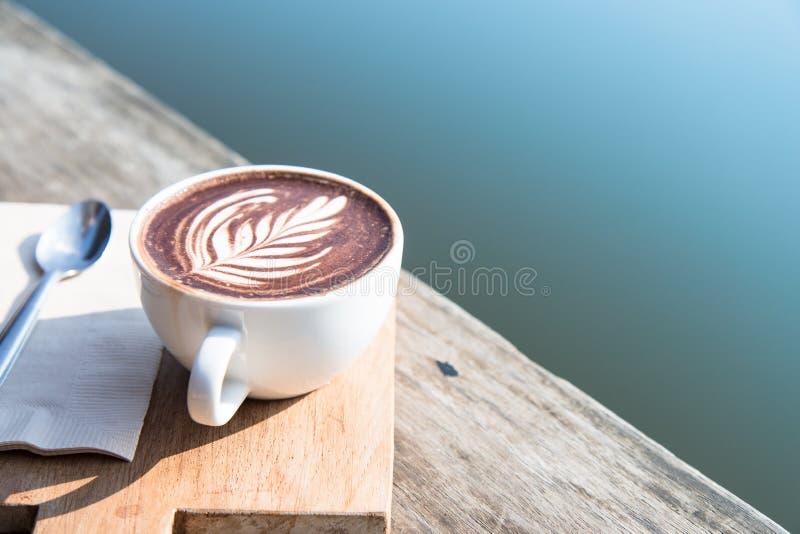 Konst för kopp för vitt kaffe med skeden, silkespapper, skärbräda på trätabellen i coffee shop bild för tappningstileffekt, royaltyfri foto