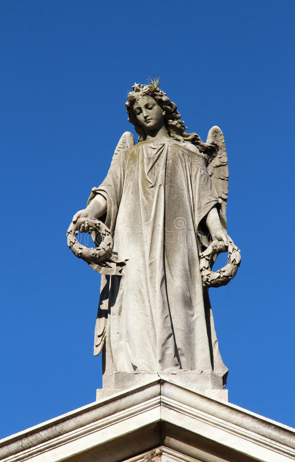 Ängeln med kranar räcker in den kvinnliga statyn. Sorg och minne. royaltyfri foto