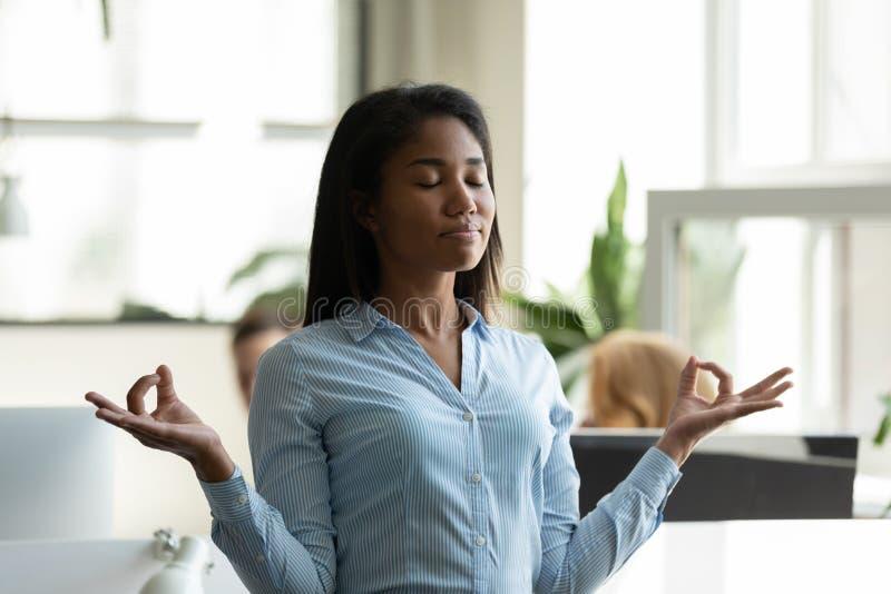 Konstaterad afrikansk amerikan affärskvinna som lättar, mediterar i yoga-attitydandövningar royaltyfria foton