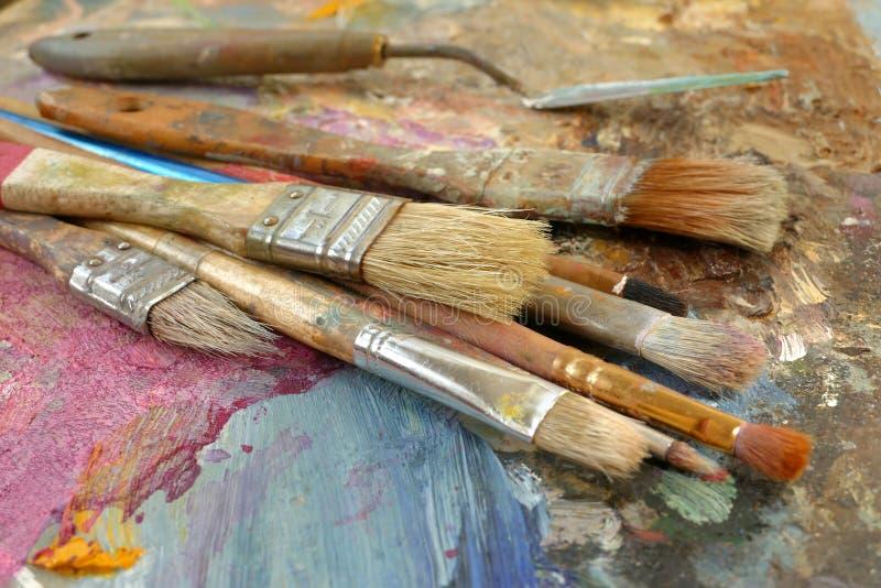 Konstborstar på en palett med målarfärg arkivbilder