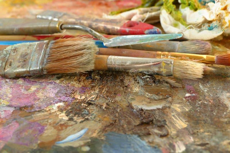 Konstborstar på en palett med målarfärger arkivbild