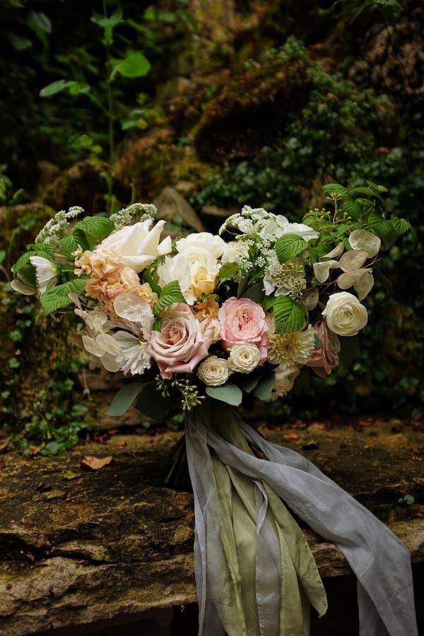 Konstbröllopbuketten i trädgården mot en bakgrund av stenar, en bukett av blommor ger bakgrunden för bröllop två arkivfoton