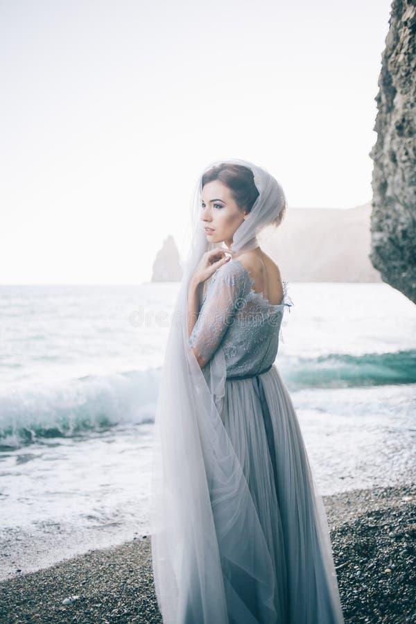 Konstfotoet av en härlig kvinna i en delikat grå färg klär på stranden i sommaren arkivbilder