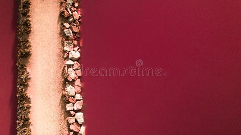 Konstgjord brobanaväg över den naturliga röda rosa färgvattensjön i Torrevieja arkivbilder