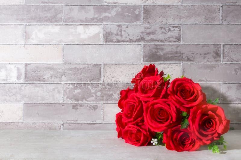 Konstgjord röd rosblommabukett på baksida för vägg för tabellgrå färgtegelsten royaltyfria bilder