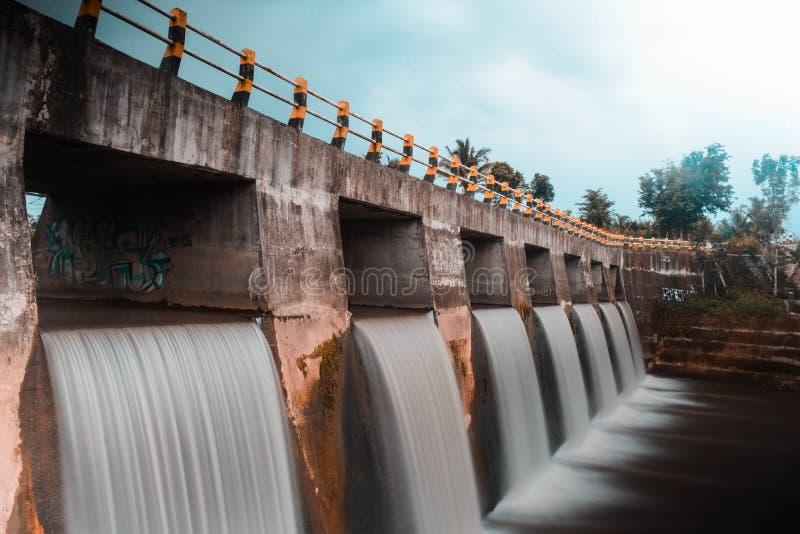 konstgjord vattenfall i floden under bron royaltyfri foto