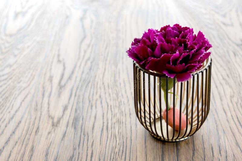 Konstgjord wood blomkruka på trätabellen, litet ljus - brun färg i rum royaltyfri foto