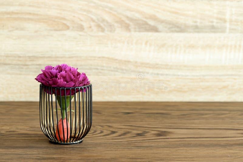 Konstgjord wood blomkruka på trätabellen, litet ljus - brun färg i rum royaltyfri fotografi