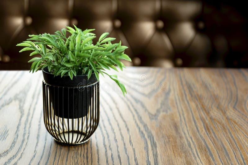 Konstgjord wood blomkruka på trätabellen, litet ljus - brun färg i rum arkivfoto