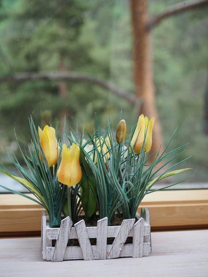 Konstgjorda blommor, i att tillverka krukor på en träfönsterbräda, ecodesign royaltyfri fotografi