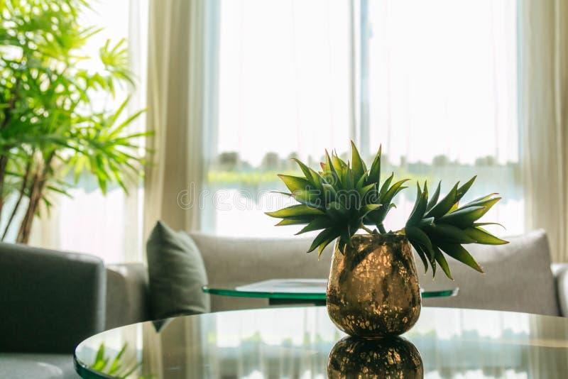 Konstgjorda blommor i en vas på en tabell i vardagsrummet royaltyfri fotografi