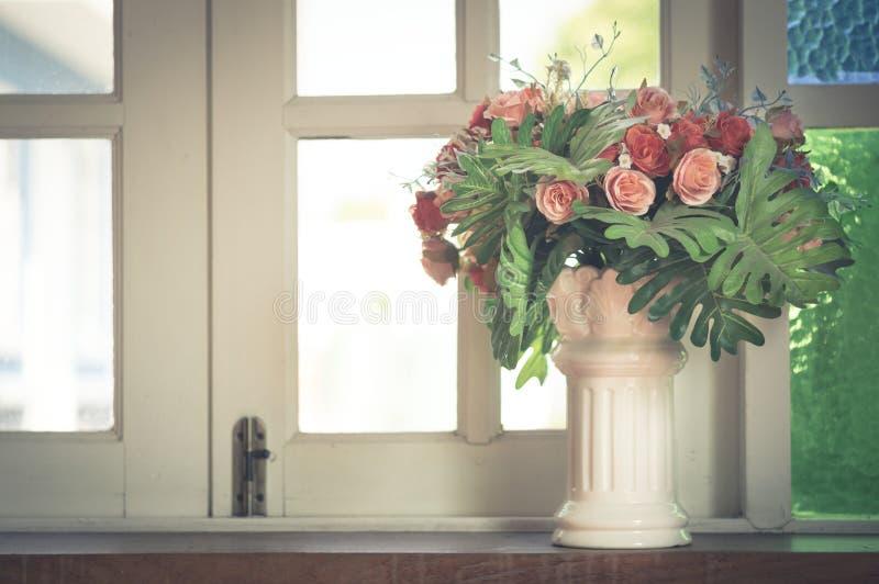 Konstgjorda blommor i vas på fönstret royaltyfri bild