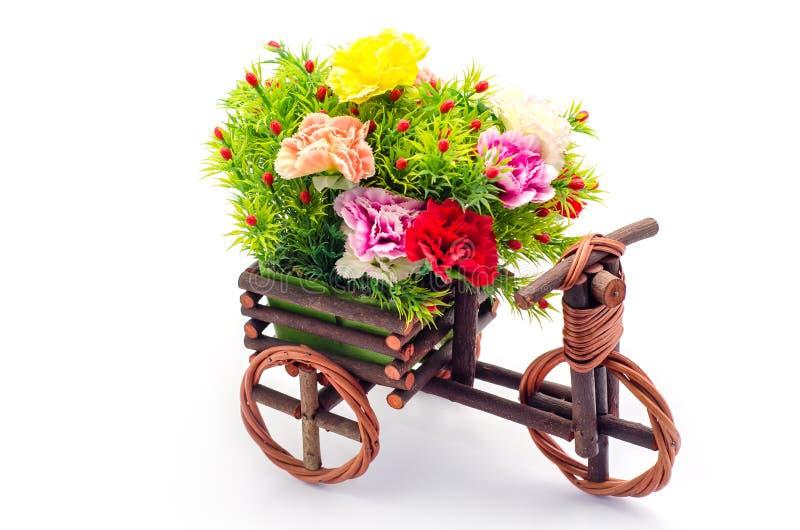 Konstgjorda blommor med trätrehjulingleksaken royaltyfri bild