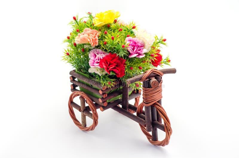 Konstgjorda blommor med trätrehjulingleksaken fotografering för bildbyråer
