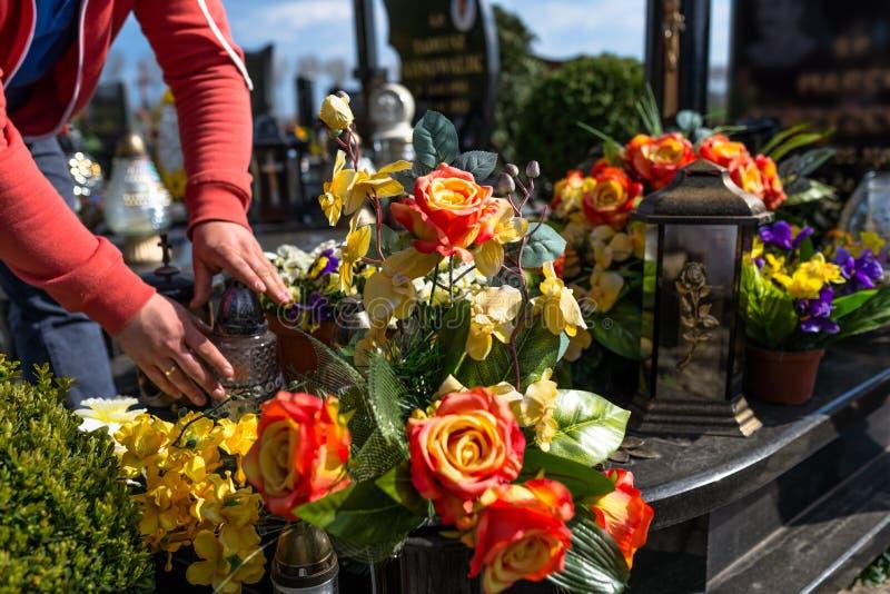 Konstgjorda blommor och ljusstakar ligger p? gravstenen i kyrkog?rden, synliga h?nder av en man arkivbilder