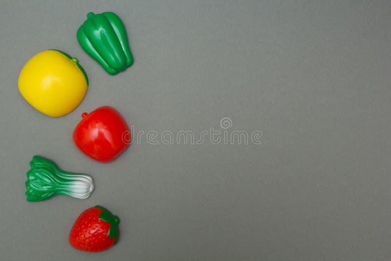 Konstgjorda frukter och grönsaker på en grå bakgrund arkivfoton