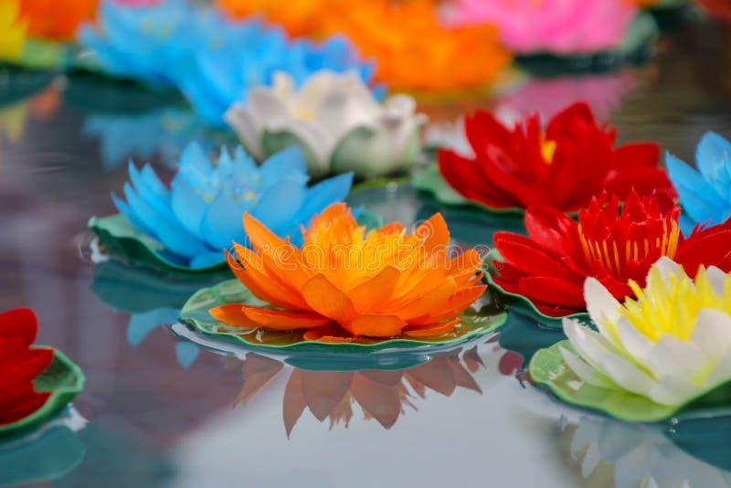 Konstgjorda lotusblommablommor i olika färger som svävar på vattenyttersidan med härlig reflexion royaltyfri fotografi