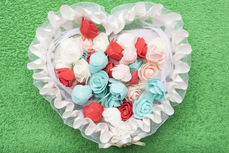 Konstgjorda mångfärgade rosor ligger i en vit snör åt korgen i form av en hjärta arkivfoton