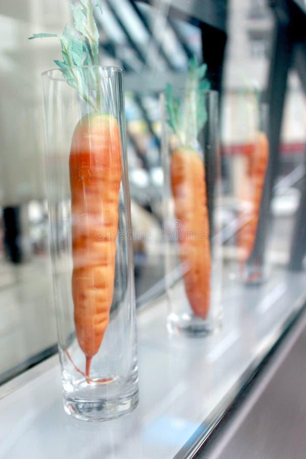 Konstgjorda morötter i långa genomskinliga exponeringsglas royaltyfri foto