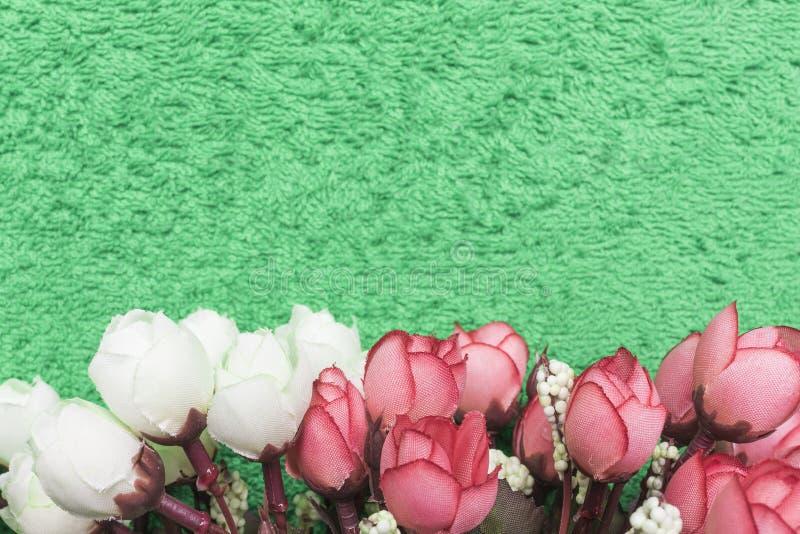 Konstgjorda vita och rosa rosor på engräsplan bakgrund som är längst ner av ramen arkivfoto