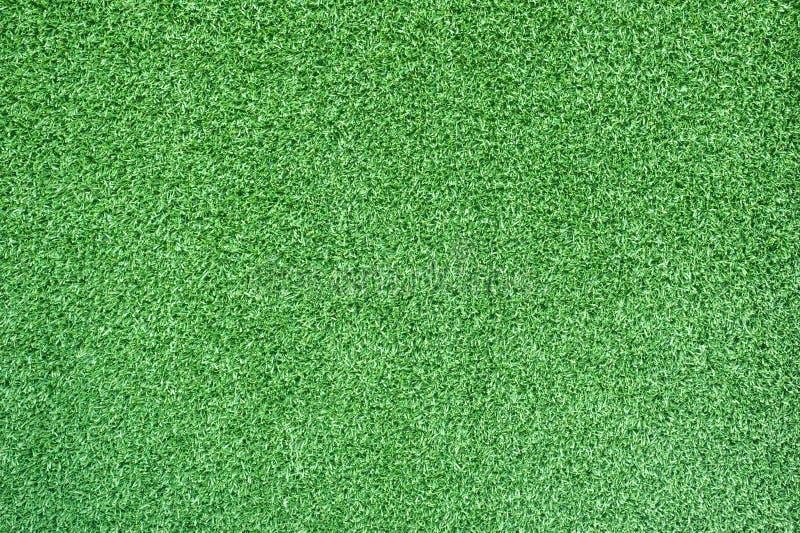 Konstgjort grönt gräs för bakgrund och fotboll arkivbilder