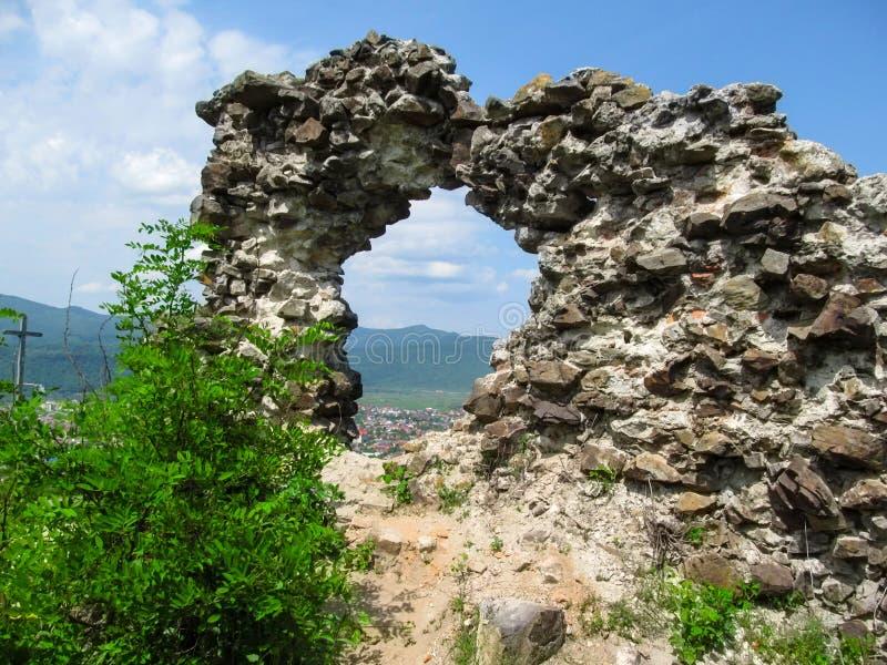Konstgjort vagga gjort från stenar med ett runt hål, som du kan se till och med att landskapet av Khust som förbluffar sikt av fö royaltyfria bilder