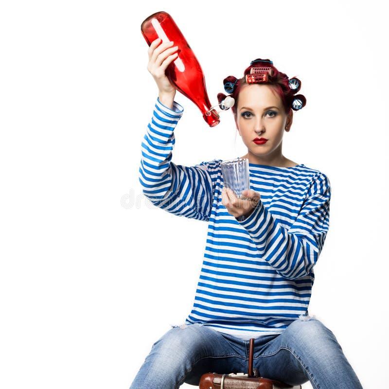 Konstig hemmafru som rymmer en tomglas av vin och exponeringsglas på en vit bakgrund Kvinnlig alkoholböjelse för begrepp royaltyfri fotografi