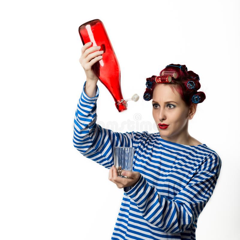 Konstig hemmafru som rymmer en tomglas av vin och exponeringsglas på en vit bakgrund Kvinnlig alkoholböjelse för begrepp royaltyfria foton