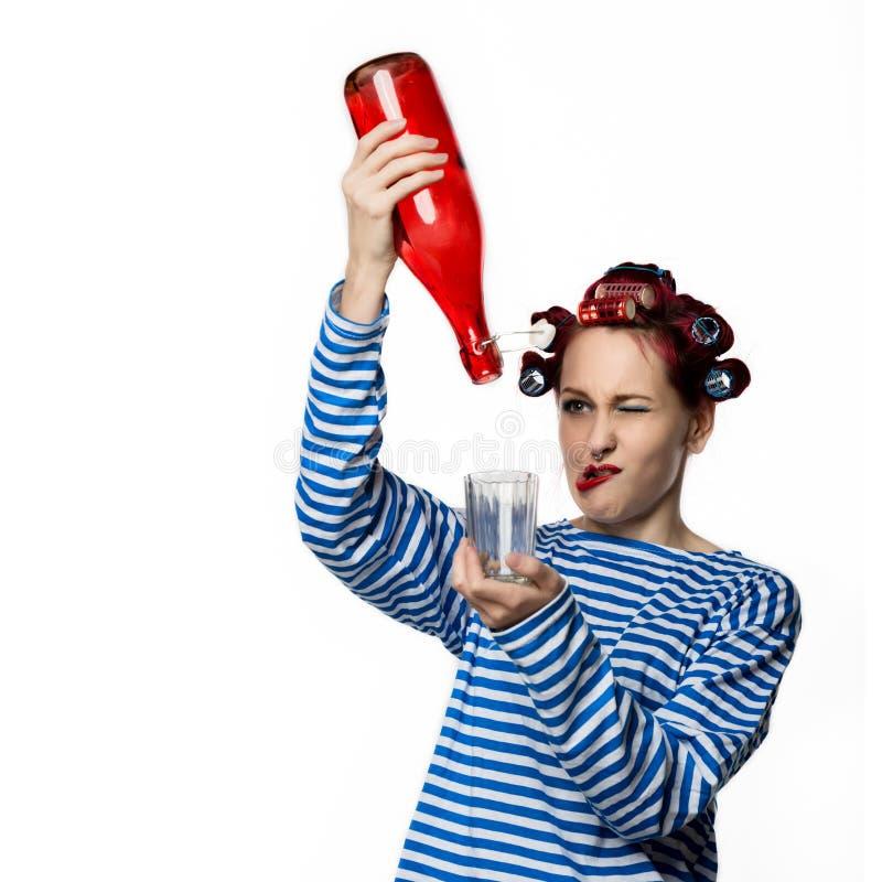 Konstig hemmafru som rymmer en tomglas av vin och exponeringsglas på en vit bakgrund Kvinnlig alkoholböjelse för begrepp royaltyfria bilder