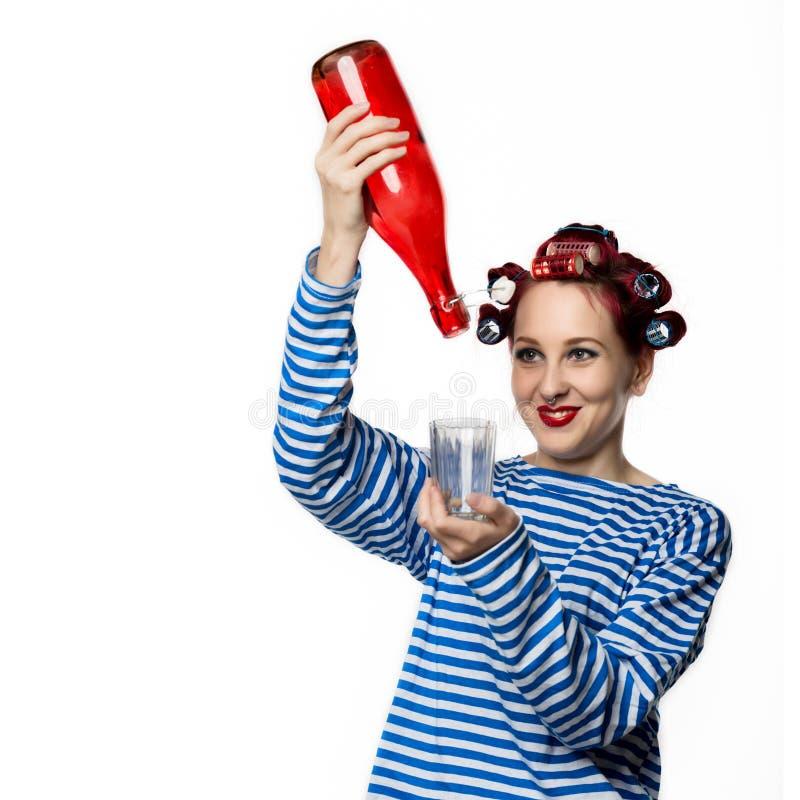Konstig hemmafru som rymmer en tomglas av vin och exponeringsglas på en vit bakgrund Kvinnlig alkoholböjelse för begrepp arkivfoton