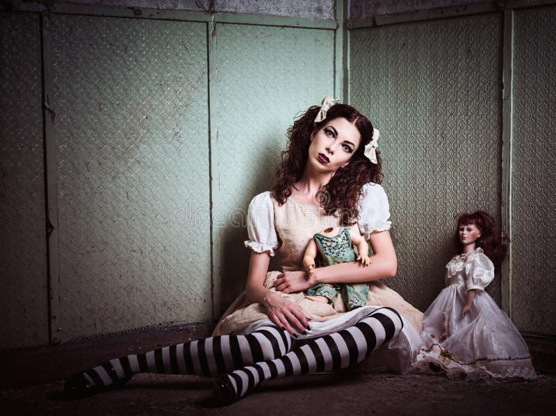 Konstig ledsen flicka med dockor som sitter i lämnat kvar ställe arkivfoto
