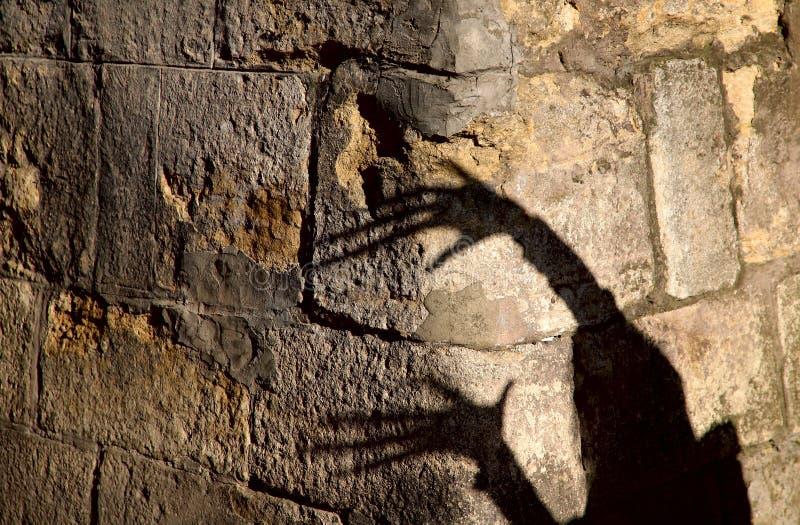 Konstig skugga av två händer på ett gammalt stenar väggen Svart skugga, kvinnlig hand royaltyfri bild