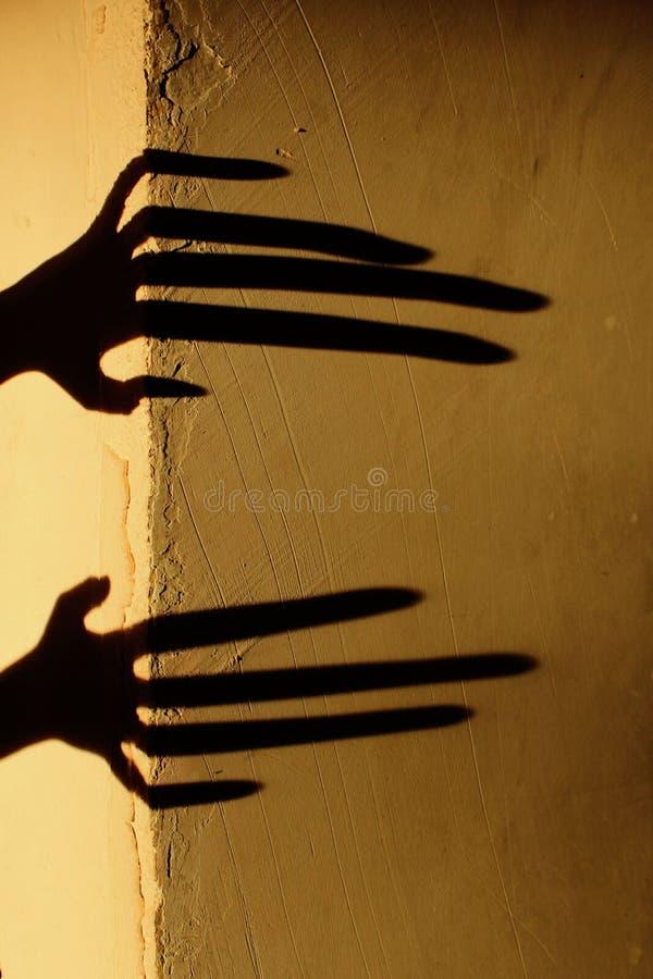 Konstig skugga p? v?ggen Ruskig skugga abstrakt bakgrund Svart skugga av en stor hand p? v?ggen Kontur av en hand på T royaltyfri bild