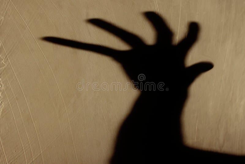 Konstig skugga p? v?ggen Ruskig skugga abstrakt bakgrund Svart skugga av en stor hand p? v?ggen Kontur av en hand på T fotografering för bildbyråer
