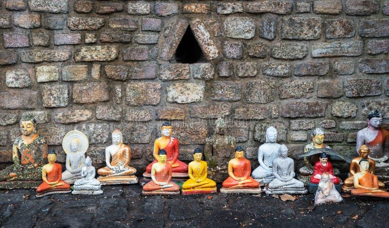 Konstiga och skadade statyetter av Buddha av det olika formatet l?ngs tegelstenv?ggen arkivbilder