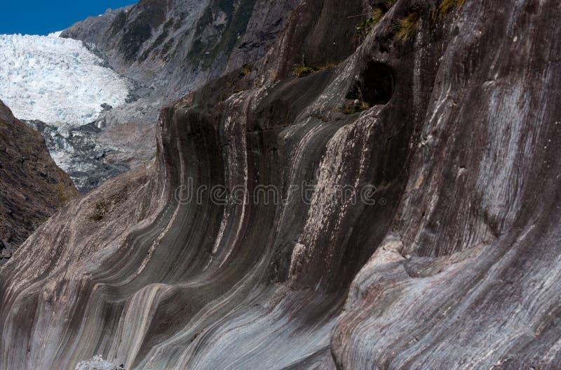 Konstigt vagga bildande i förgrunden och Franz Josef Glacier i bakgrunden i Mten Laga mat/den Aoraki nationalparken in royaltyfri bild
