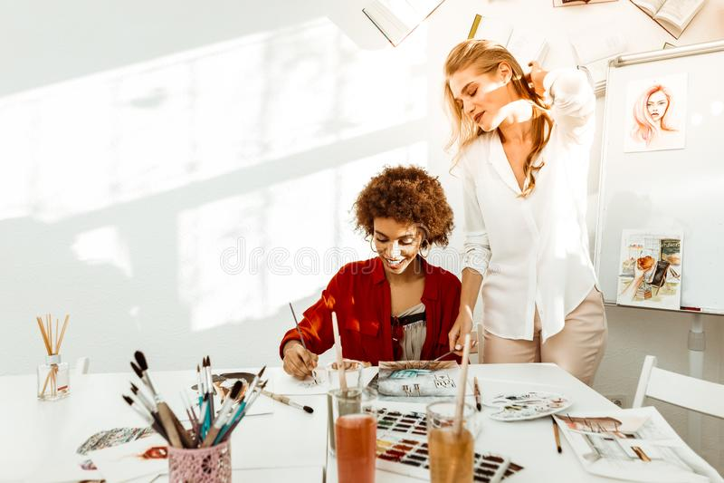 Konstlärare som bär beige byxa och det vita blusanseendet nära student royaltyfria bilder