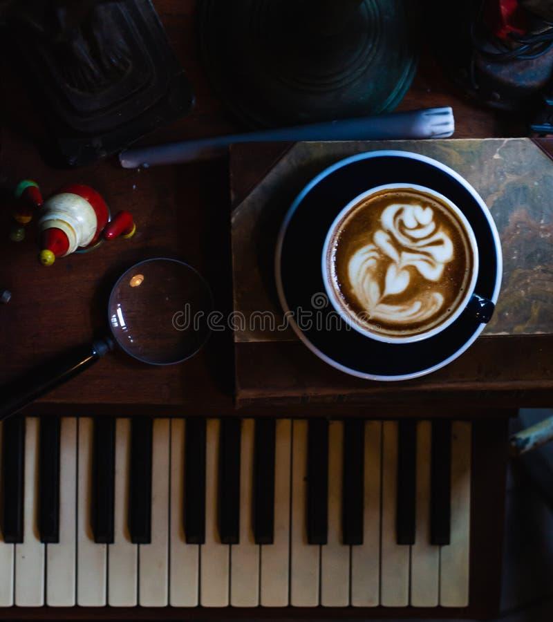 Konstlatte per koppen av varmt kaffe på piano royaltyfri fotografi