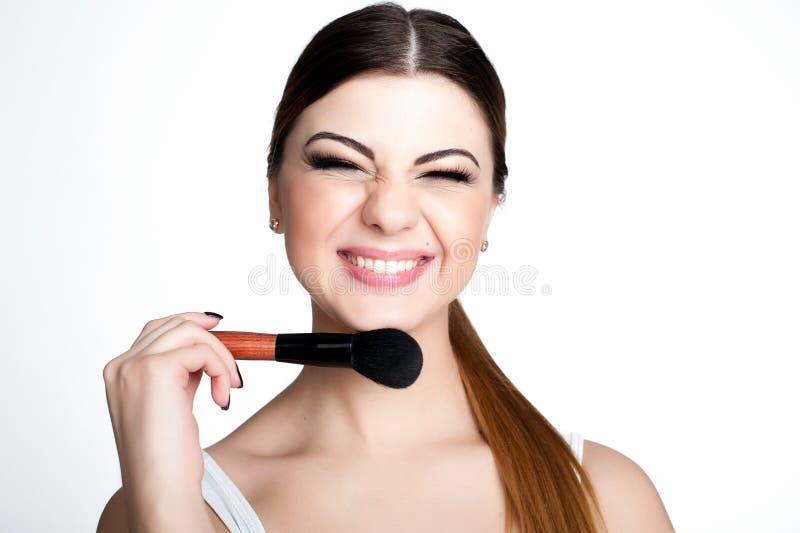 Konstnär för skönhetflickasmink med makeupborsten Ljust feriesmink för brunettkvinna med bruna ögon härlig framsida makeover royaltyfri fotografi