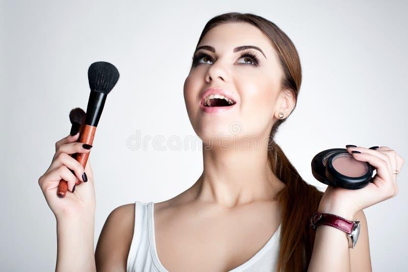 Konstnär för skönhetflickasmink med makeupborsten Ljust feriesmink för brunettkvinna med bruna ögon härlig framsida makeover arkivbilder