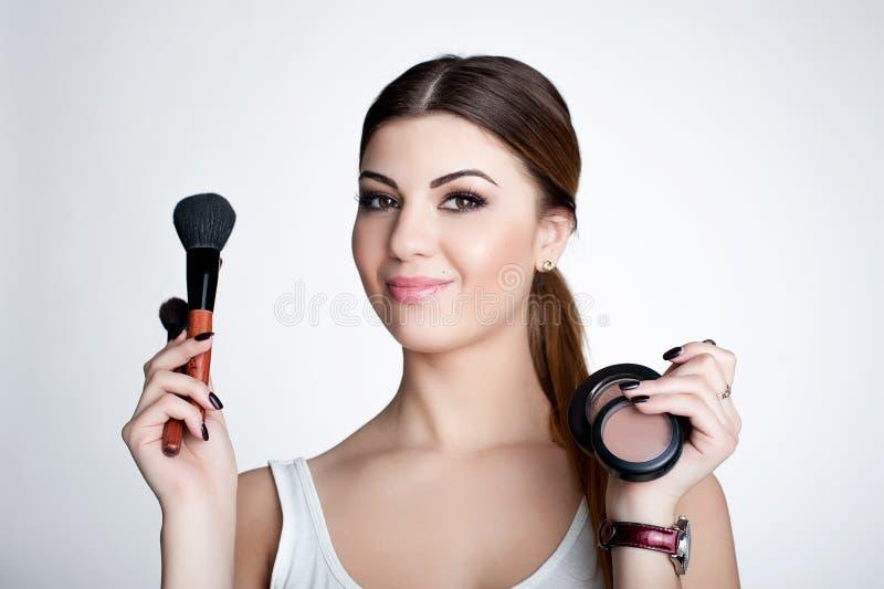 Konstnär för skönhetflickasmink med makeupborsten Ljust feriesmink för brunettkvinna med bruna ögon härlig framsida makeover arkivbild