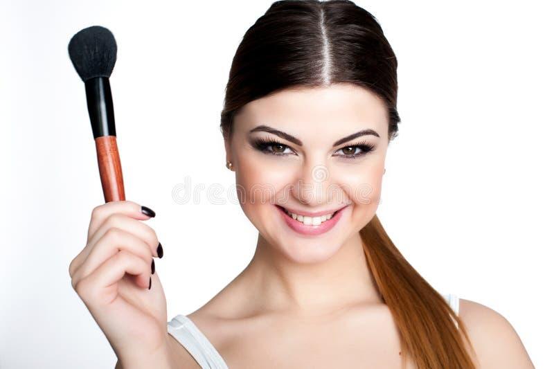 Konstnär för skönhetflickasmink med makeupborsten Ljust feriesmink för brunettkvinna med bruna ögon härlig framsida makeover arkivfoton